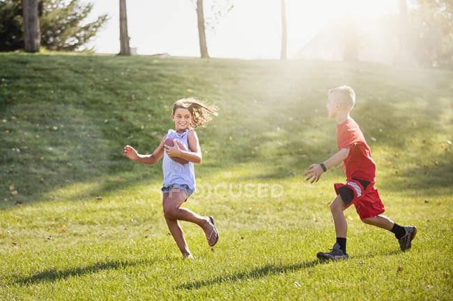 Дівчинка і хлопчик грають американський футбол — стокове фото