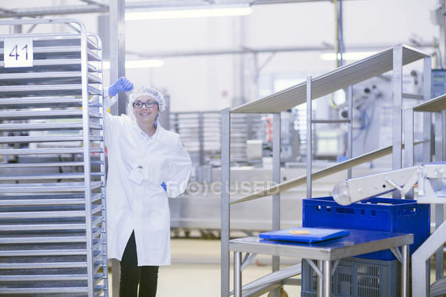 Factory worker wearing hair net looking at camera smiling — Stock Photo