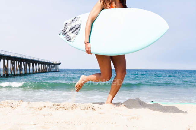 Mujer que corre con tabla de surf, Hermosa Beach, California, Usa - foto de stock