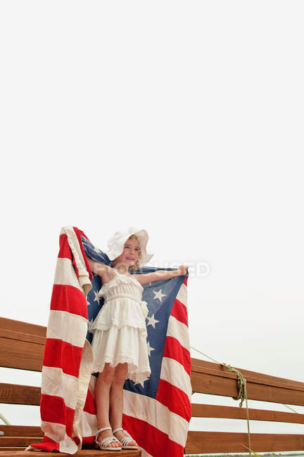 Girl holding US flag outdoors — Stock Photo