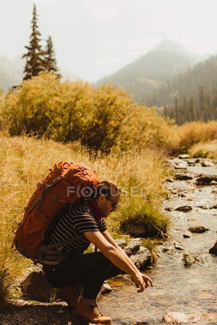 Mann mit Rucksack am Bach sitzend, Mineral King, Sequoia National Park, Kalifornien, USA — Stockfoto