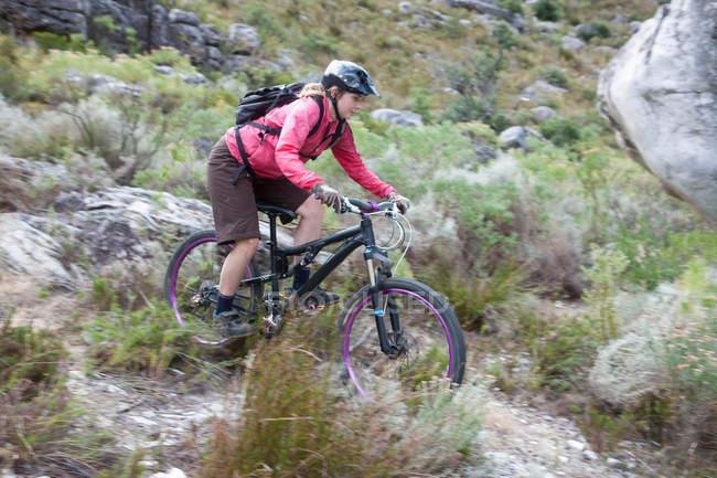 Joven mujer bicicleta de montaña a través de matorrales - foto de stock