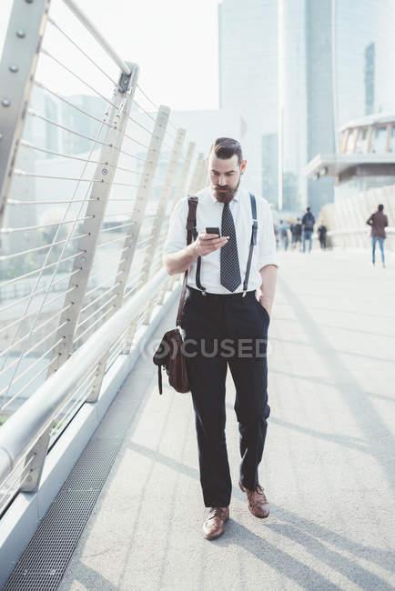 Homme d'affaires lisant la mise à jour du texte du smartphone en marchant sur la passerelle — Photo de stock