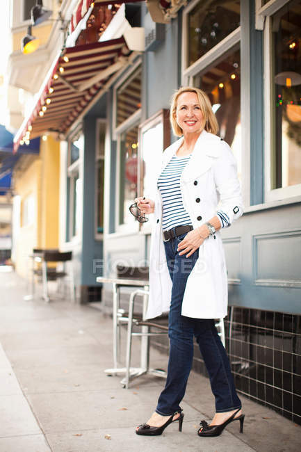 Зрелая женщина в белом халате и джинсах ходит по улице — стоковое фото