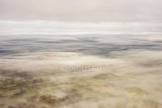 Land seen through thin layer of clouds — Stock Photo