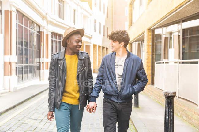 Гомосексуальная пара на улице, держась за руки лицом к лицу, улыбаясь — стоковое фото