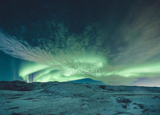 Aurora Boreal ilumina el cielo sobre paisaje cubierto de nieve - foto de stock