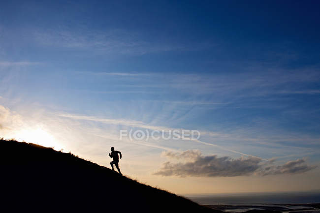 Silhouette of hiker running up hillside — Stock Photo