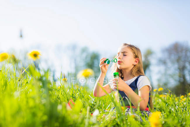 Girl blowing bubbles in field — Stock Photo