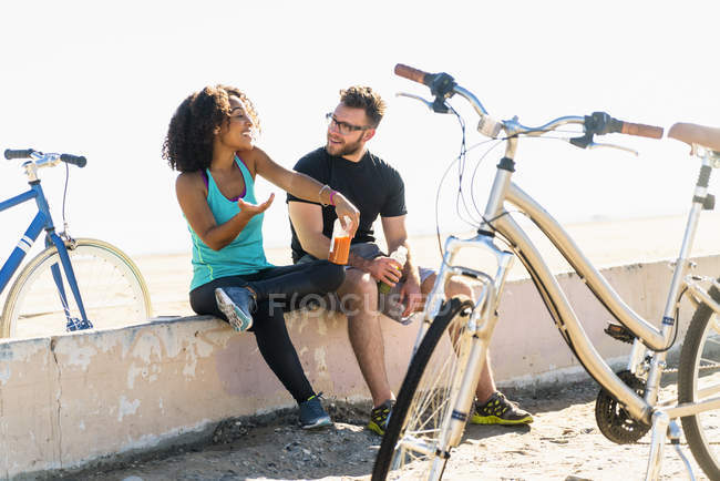 Couple sitting on wall, taking a break, bicycles beside them — Stock Photo