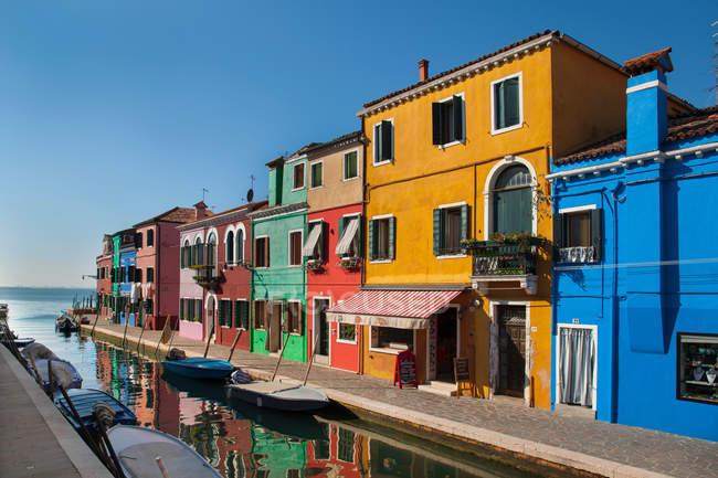 Bâtiments colorés au-dessus de canal d'eau en plein soleil — Photo de stock