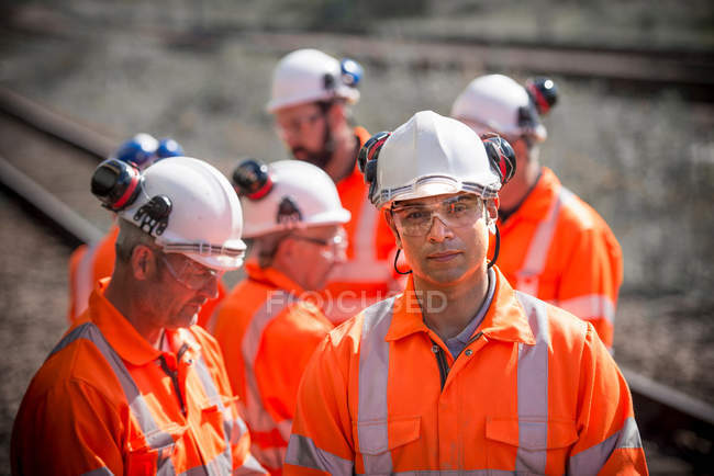 Portrait of railway worker with colleagues wearing protective clothing — Stock Photo