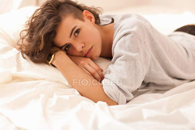 Young woman lying on bed, portrait — Stock Photo