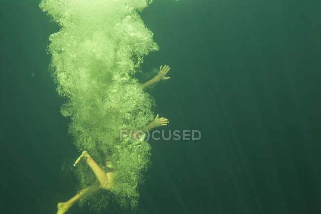 Front view of boy with obscured face swimming underwater — Stock Photo