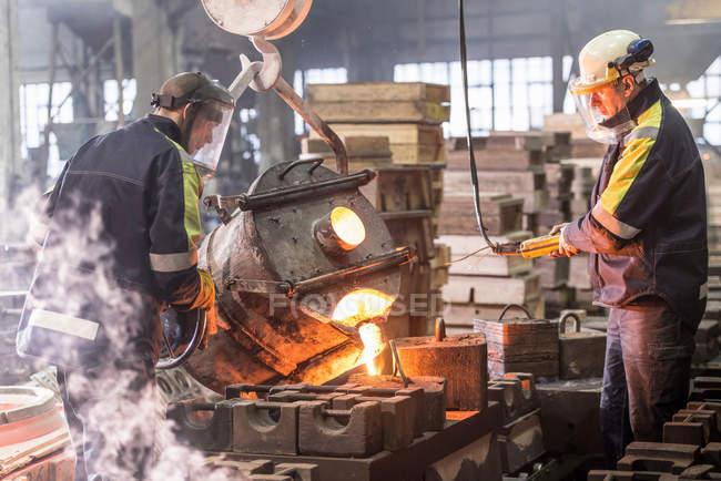Arbeiter gießen in Gießerei geschmolzenes Metall in Formen — Stockfoto