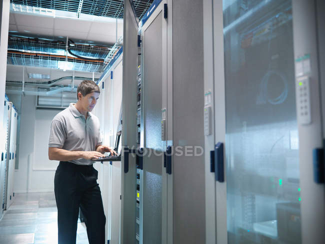 Man working in computer server room — Stock Photo