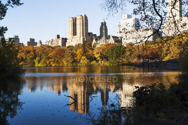 Reflejo de rascacielos y árboles en el lago Central Park - foto de stock
