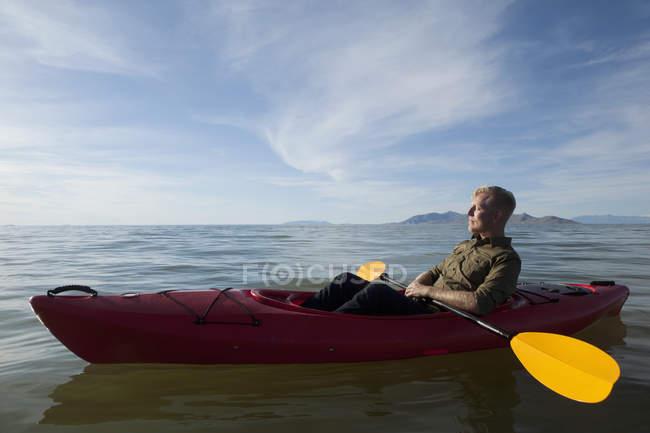 Seitenansicht des Jünglings im Kajak auf dem Wasser halten Paddel, Augen geschlossen, Great Salt Lake City, Utah, Usa — Stockfoto