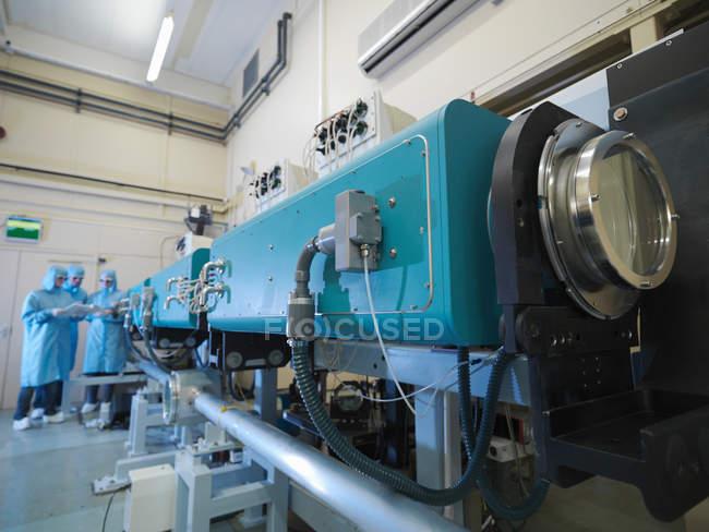 Wissenschaftler im Labor, mit großem Lasergerät im Vordergrund — Stockfoto