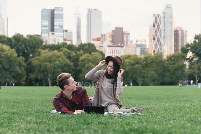 Mulher adulta média experimentando chapéu de feltro para namorado em Central Park, Nova York, EUA — Fotografia de Stock