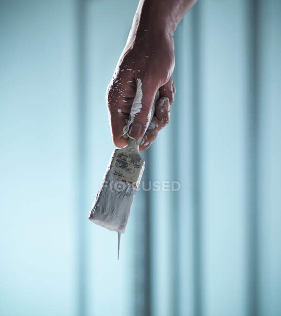 Man holding paint brush with white paint dripping — Stock Photo