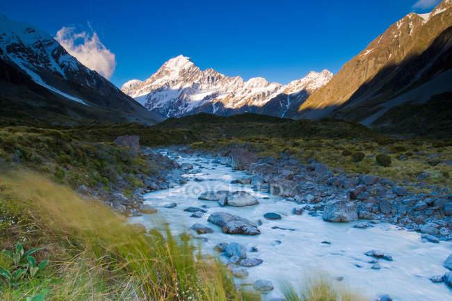 Schneebedeckte Berge und ländliche creek — Stockfoto