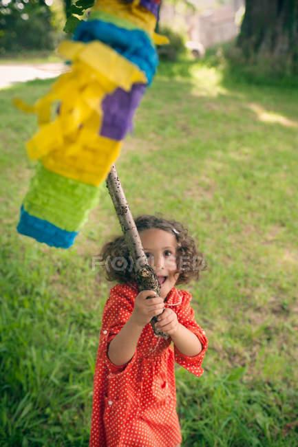 Chica balanceándose en piñata en fiesta - foto de stock