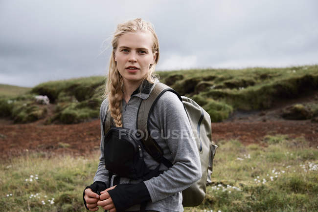 Hiker carrying backpack on hillside — Stock Photo