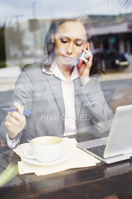 Young female businesswoman taking on smartphone in cafe — Stock Photo