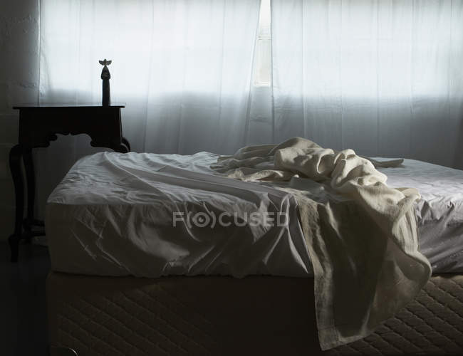 Unmade bed in morning light — Stock Photo