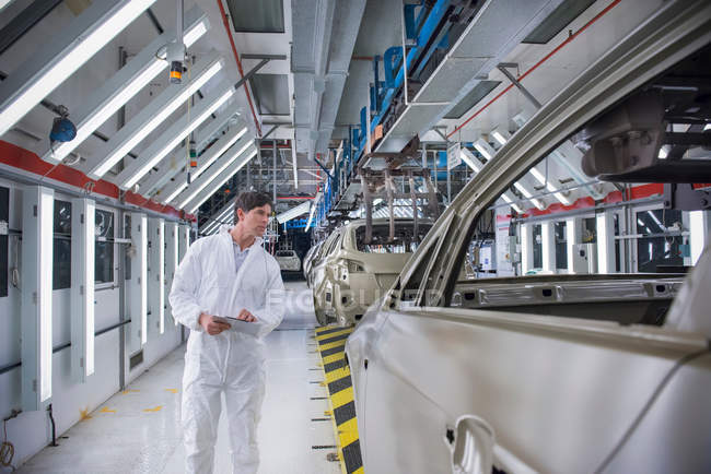 Worker inspecting car body in car factory — Stock Photo