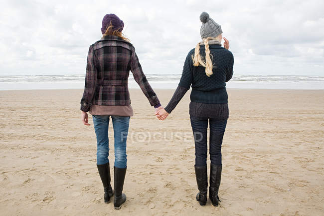 Women holding hands at the beach — Stock Photo