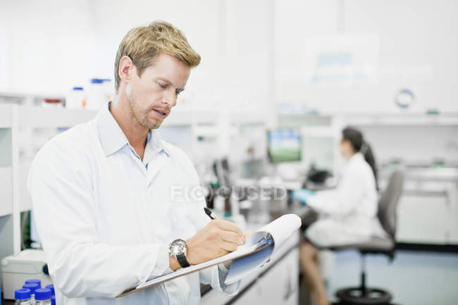 Scientifique écrivant sur presse-papiers en laboratoire — Photo de stock