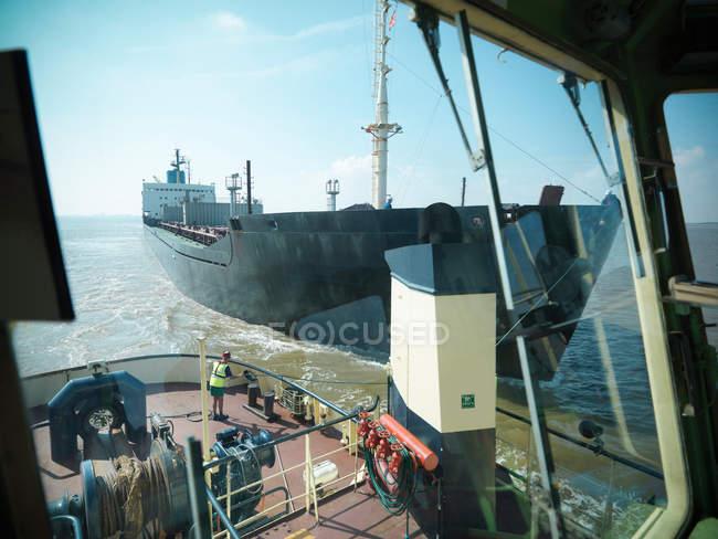 Vista dal ponte del rimorchiatore del marinaio che tira le linee di traino per spedire in mare — Foto stock
