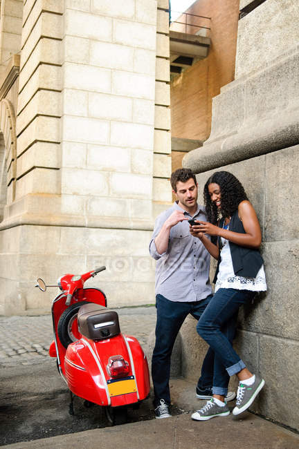 Couple by scooter, looking at cellphone — Stock Photo