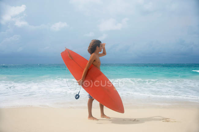 Man carrying surfboard on tropical beach — Stock Photo