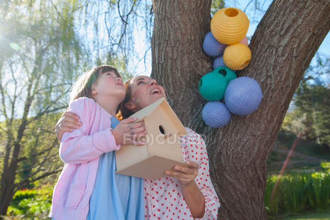 Mother and daughter holding birdhouse — Stock Photo