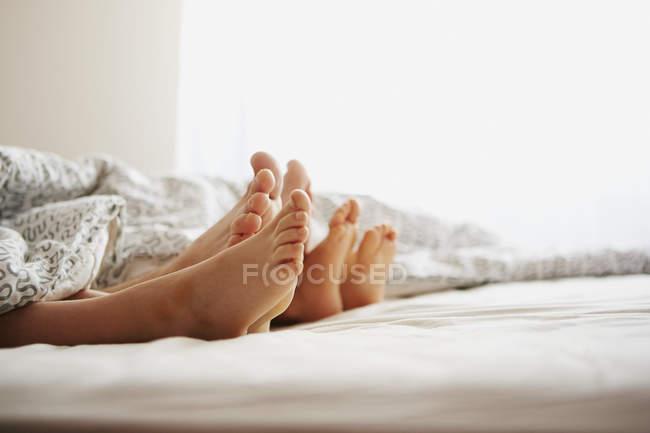 Голые ноги родителей и лежащего в постели сына — стоковое фото