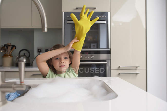 Girl pulling on rubber glove at sink — Stock Photo