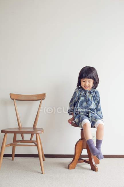 Menina sentada no banquinho, retrato — Fotografia de Stock