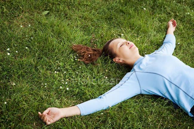 Женщина лежит в траве в парке — стоковое фото