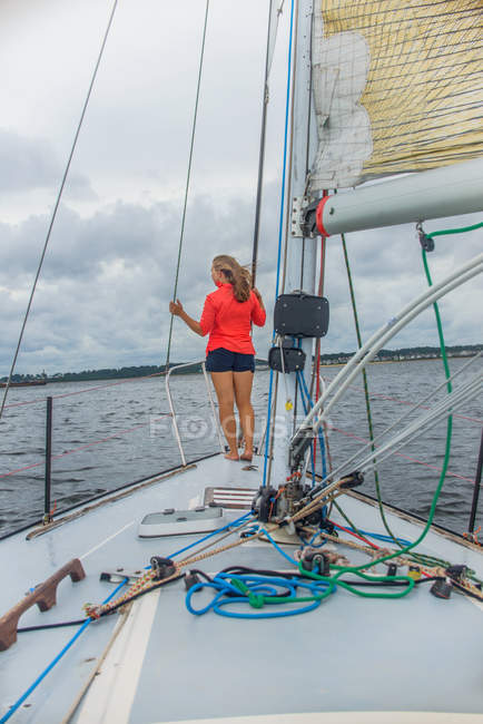 Full length rear view of young woman on bow of sailboat looking away — Stock Photo