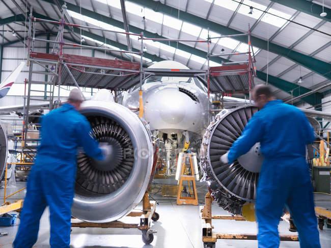 Engenheiros de aeronaves que inspeccionam motores a jacto de avião a jacto — Fotografia de Stock