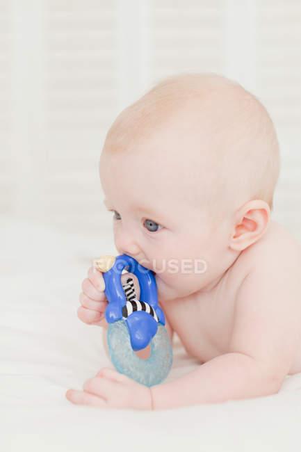 Ребенок жевательной на погремушка в постели — стоковое фото