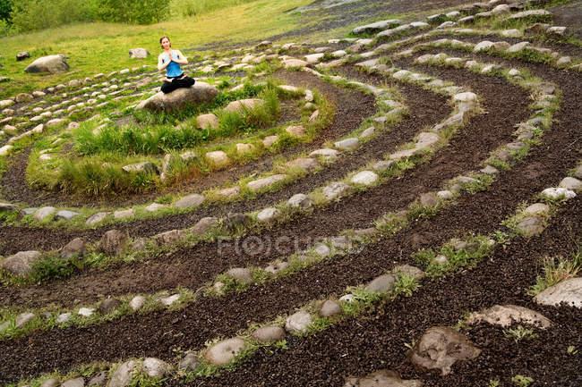 Femme méditant dans le labyrinthe de pierre — Photo de stock