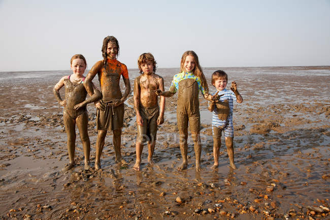 Children covered in mud on rocky beach — Stock Photo