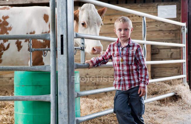 Ritratto di Ragazzo con mucca in fienile — Foto stock