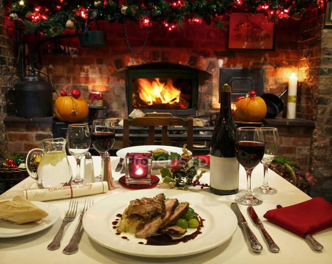 Mesa servida junto a la chimenea para cena de Navidad - foto de stock