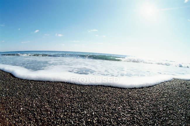 Прибой на галечный пляж — стоковое фото
