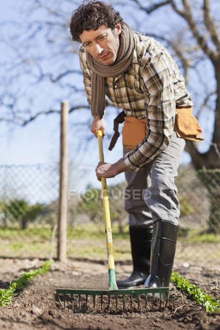 Man turning over soil in garden — Stock Photo